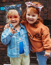 Load image into Gallery viewer, Girl in orange jumper and  headland  and toddler in denim jacket