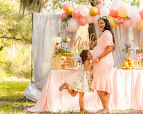 Pregnant woman at baby shower and little girl kissing tummy
