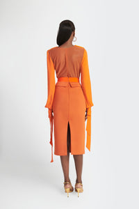Statement blouse with exaggerated lapels and bow tie cuffs in orange by Sukeina back view