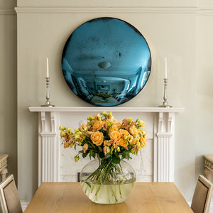 Aged Blue Convex Round Mirror placed on a white mantlepiece and flanked by candles