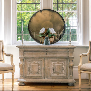 Aged Bronze Round Convex Mirror propped on a wooden sideboard in front of a bay window