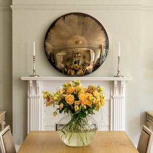 Aged Bronze Round Convex Mirror above a period mantlepiece and flanked by candles