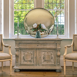 An aged silver round convex mirror on a wooden sideboard in front of a large bay window