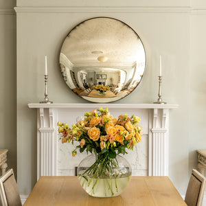 An aged silver round convex mirror on the mantlepiece of a traditional fireplace