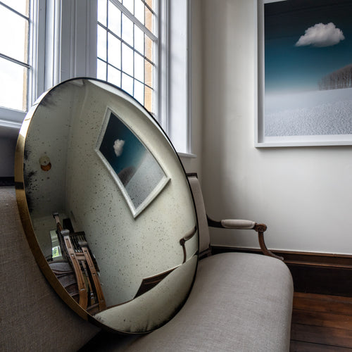 An aged silver mirror propped on a sofa and reflecting a painting  of blue sky and clouds