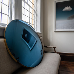 A Blue Round Convex Mirror propped on a traditional sofa. The Mirror reflects a landscape painting of  blue sky, trees and white clouds.