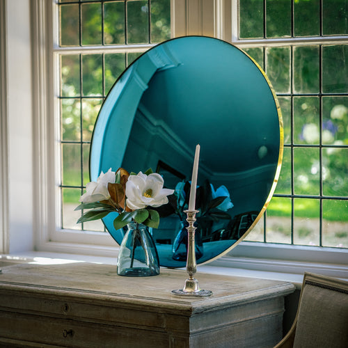 A Blue Round Convex Mirror propped on a wooden sideboard and against a large bay window. A vase of flowers and candle stick is placed in front of the mirror.
