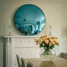 Load image into Gallery viewer, A Blue Round Convex Mirror placed on the mantelpiece of a traditional fireplace, and flanked by candles. A dining room table with a vase of yellow flowers is in the foreground.