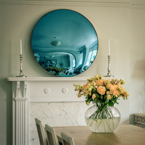 A Blue Round Convex Mirror placed on the mantelpiece of a traditional fireplace, and flanked by candles. A dining room table with a vase of yellow flowers is in the foreground.