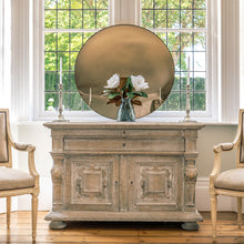 Load image into Gallery viewer, A Bronze Round Convex Mirror is propped on a rustic wooden sideboard and against a large bay window. A vase with two white flowers is on the sideboard  in front of the mirror and flanked by candles.