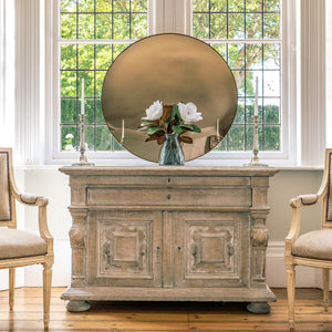A Bronze Round Convex Mirror is propped on a rustic wooden sideboard and against a large bay window. A vase with two white flowers is on the sideboard  in front of the mirror and flanked by candles.