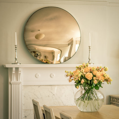 A Bronze Round Convex Mirror propped in a mantelpiece of a traditional fireplace and flanked by candles. A dining table, chairs and vase of yellow flowers is in the foreground.