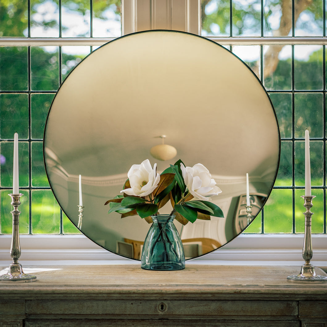 A Silver Round Convex Mirror propped on a sideboard which sites in front of a bay window