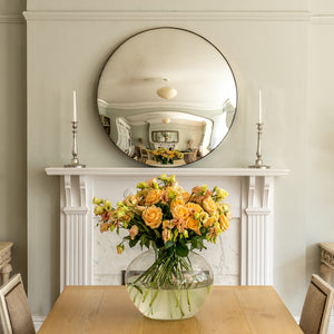A Silver Round Convex Mirror propped on the  mantelpiece of a traditional fireplace with a dining table and vase of yellow flowers in the foreground