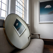 Load image into Gallery viewer, A Silver Round Convex Mirror propped on a traditional sofa and reflecting a wall landscape painting of blue sky and clouds