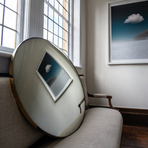 A Silver Round Convex Mirror propped on a traditional sofa and reflecting a wall landscape painting of blue sky and clouds