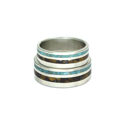 Two silver wedding bands with turquoise and brown stripes of stone inlay