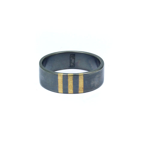 Wide wedding band with dark patina and three stripes of gold inlay