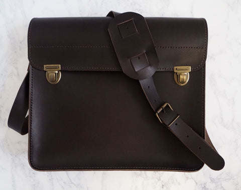 Dark brown leather satchel with brass clasps