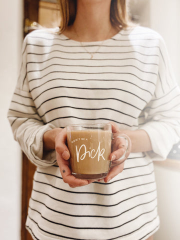 Glass mug filled with tea, white decals reading 'don't be a dick'