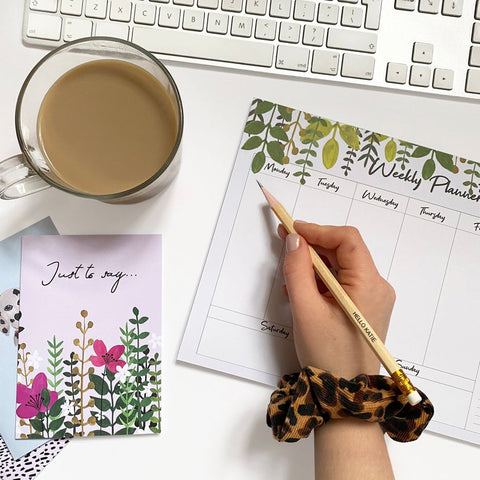 weekly planner with botanical design and cup of tea next to it