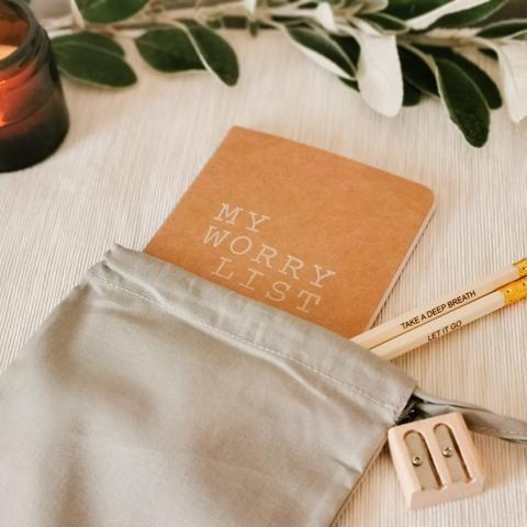 Brown kraft notebook with 'Worry List' stamped on, with two pencils, a pencil sharpener and a grey cotton gift bag