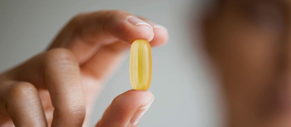 A person holding an Omega 3 supplement