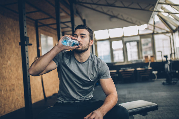 A man drinking water after having used some keto diet supplements