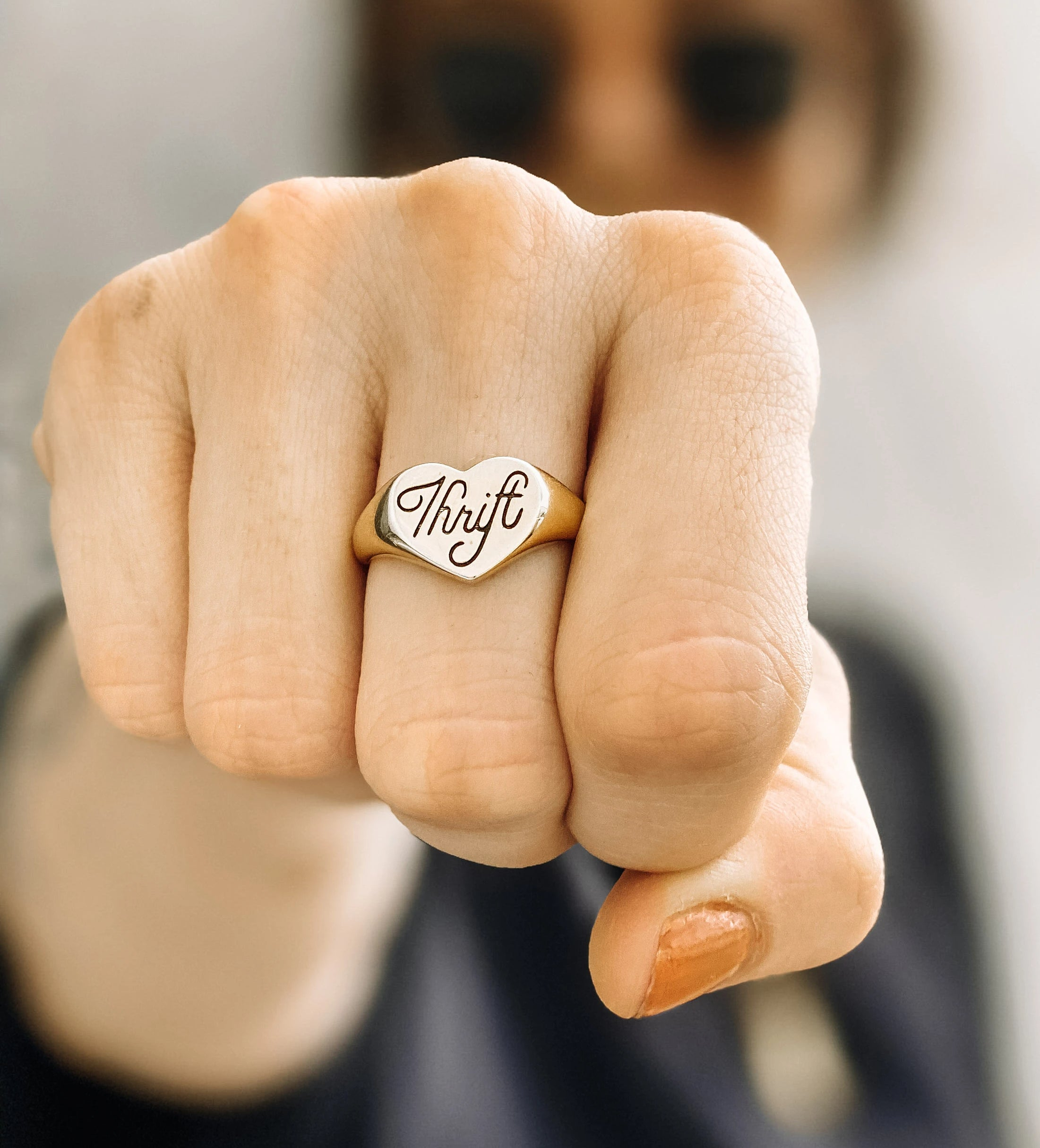 Thrift Ring worn on a fist in the camerea