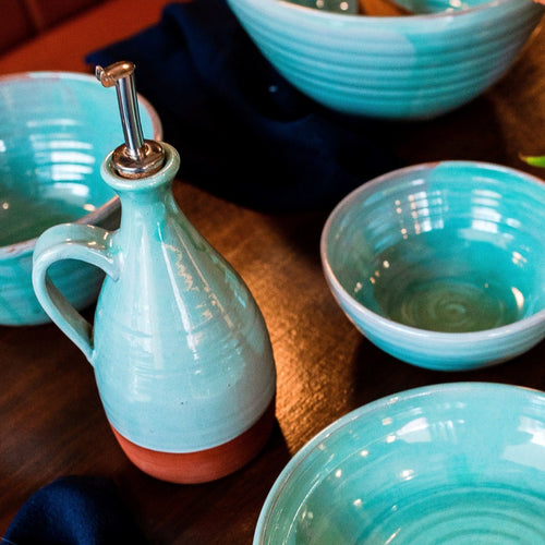 Turquoise oil pourer and 4 bowls sitting on a dark wooden table