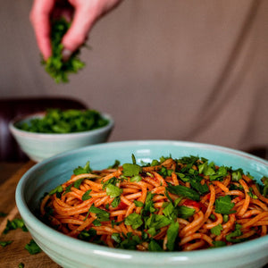 Turquoise pasta bowl with spaghetti sprinkled with pasta.  Hand in the background holding parsley.
