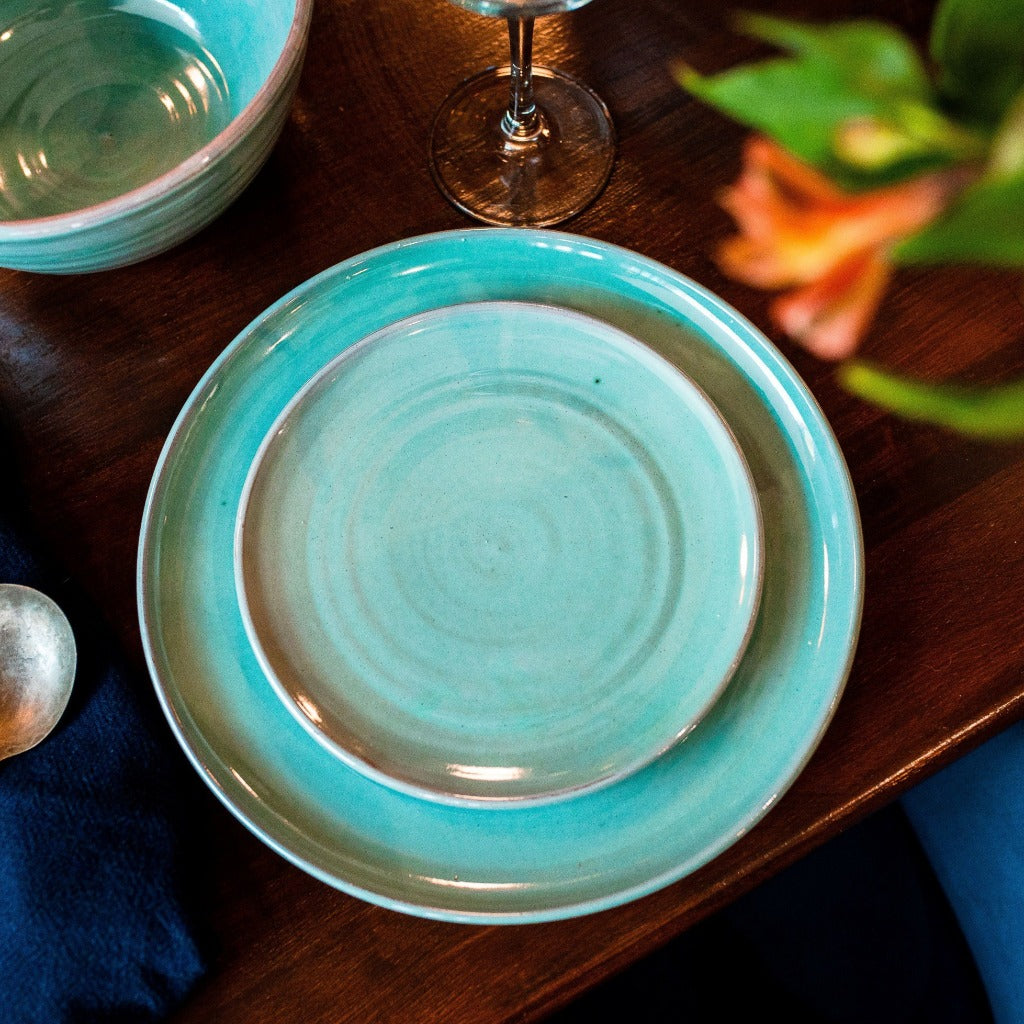 Turquoise side plate sitting on a turquoise dinner plate on a dark wooden table.