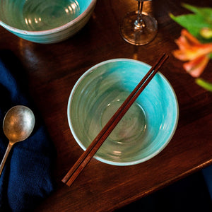 Turquoise bowl with chopsticks from above on a dark wooden table.