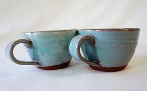 2 turquoise espresso cups side by side on a white background