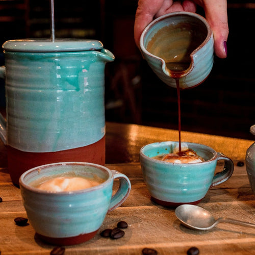 2 turquoise espresso cups with ice cream in them, espresso coffee being poured into one of the espresso cups from a mini jug with a turquoise coffee pot in the back ground