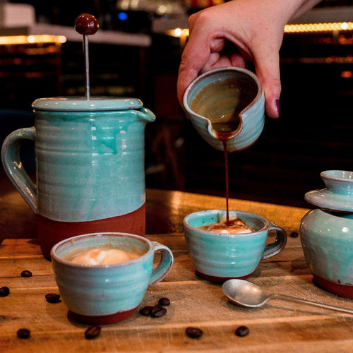 Turquoise cafetiere with 2 espresso cups and coffee being poured from a turquoise mini jug.