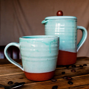 Large turquoise mug and cafetiere on a wooden board with coffee beans scattered around.