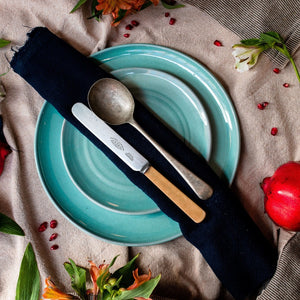 A turquoise side plate sitting on a turquoise dinner plate with a navy napkin, knife and spoon ontop. On a beige tablecloth with flowers and pomegranate scattered around.