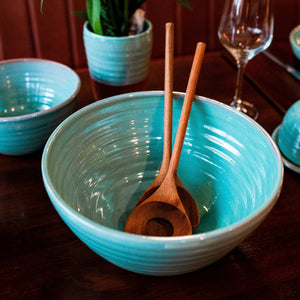 Large turquoise bowl with 2 wooden serving spoons inside. A turquoise bowl, vase and wine glass in the background.