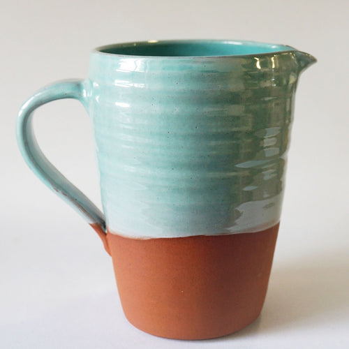 Large turquoise jug on a white background