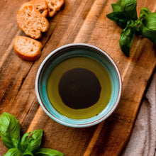 Load image into Gallery viewer, Small turquoise bowl with olive oil and balsamic on a chopping board with mini bread slices and basil.