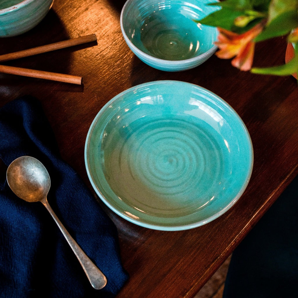 Turquoise pasta bowl on a dark table with navy napkin and soup spoon.