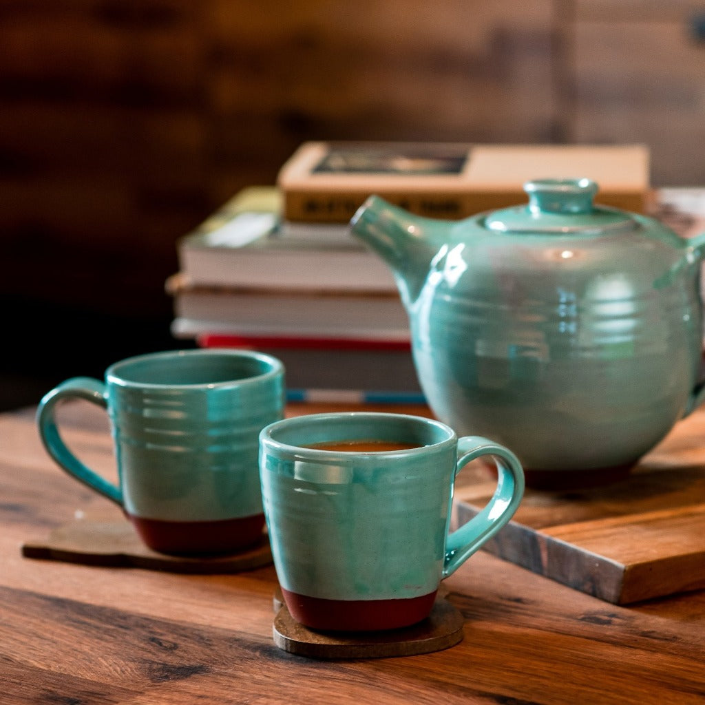 2 turquoise mugs and a turquoise teapot sitting on a wooden table with books in the background.
