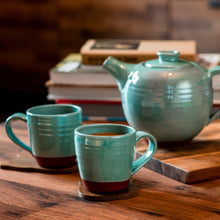 Load image into Gallery viewer, 2 turquoise mugs and a turquoise teapot sitting on a wooden table with books in the background.