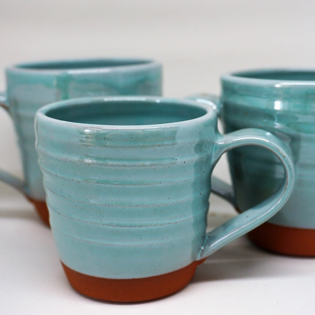 3 turquoise mugs on a white background