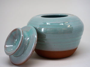 Turquoise jar with a lid leaning against iton a white background.