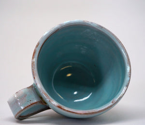 Turquoise espresso cup on it's side on a white background