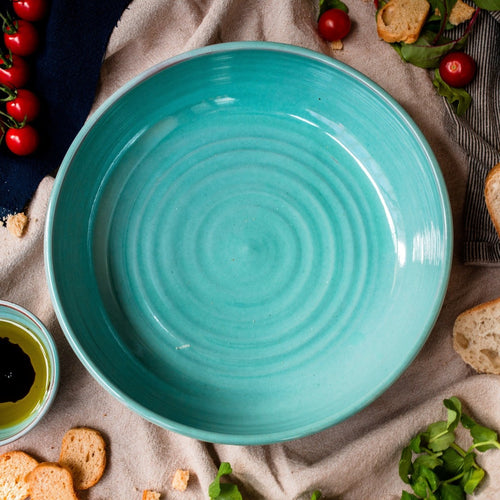 Wide shallow turquoise Bowl seen from above with tomatoes rocket and bread around it.