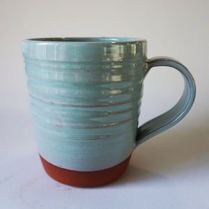 Turquoise mug on a back round
