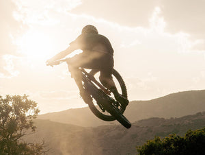 mountain biker jumping with sunset and mountains